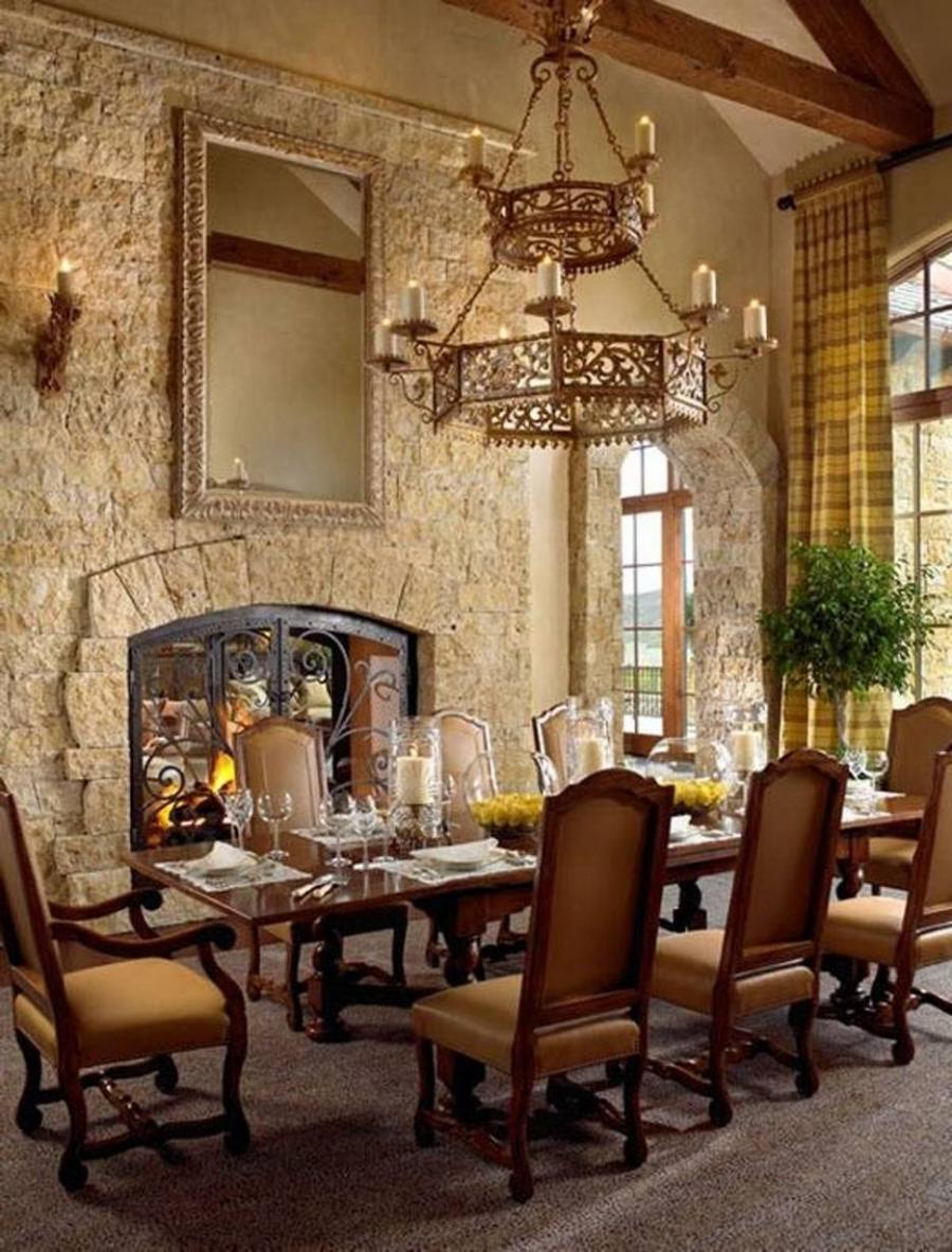 tuscan style dining room with stacked stone fireplace and sconces...