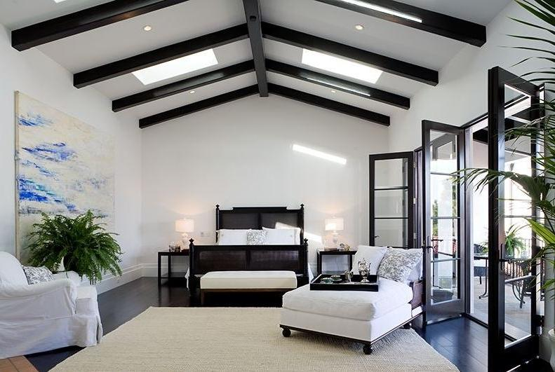 Master bedroom in a Spanish Revival home with exposed painted...