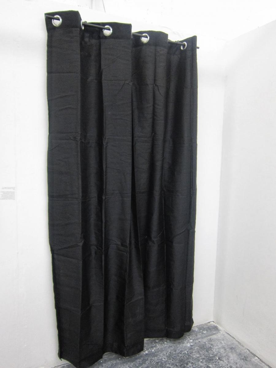 black curtain falls against the white studio wall curtains