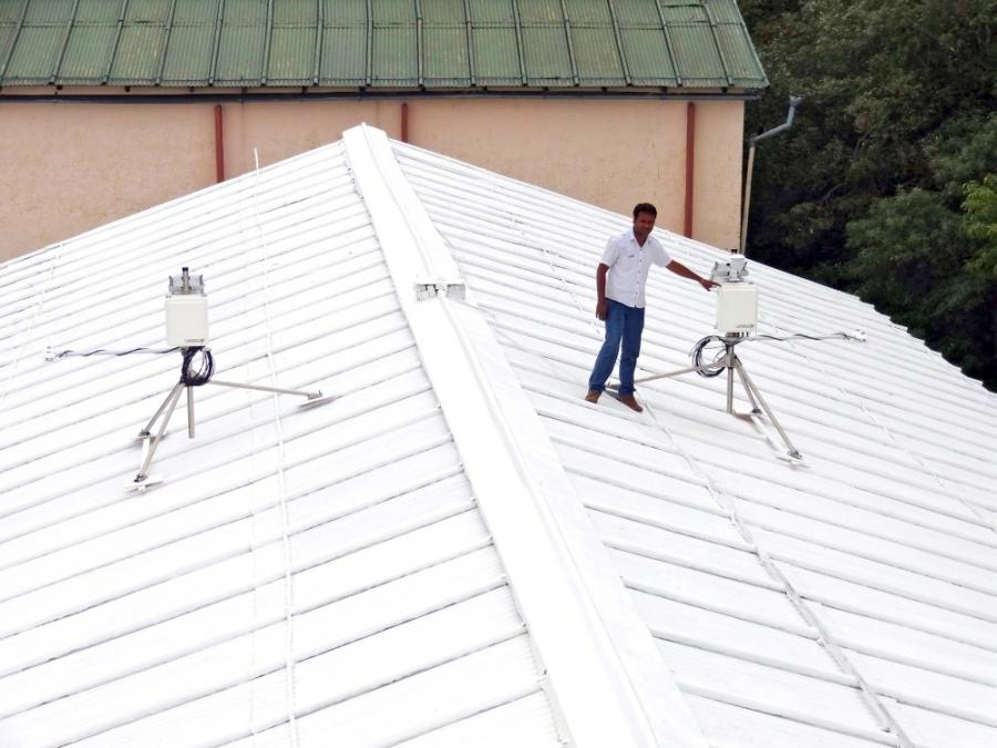 An Indian worker helps set up radiometers on a white roof. (Photo...