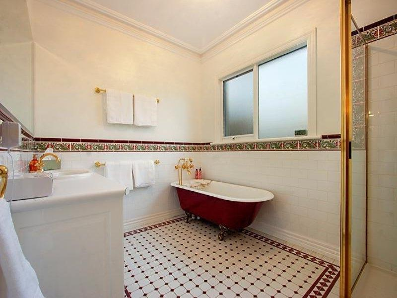French provincial bathroom design with claw foot bath using tiles...