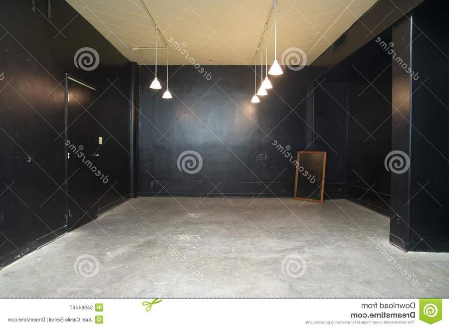 Empty room painted in black with cement and lamps hanging from...
