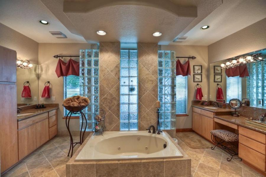 ... whirlpool tub in front of a dual entry doorless shower with...