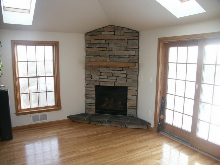 Stacked stone faced corner fireplace