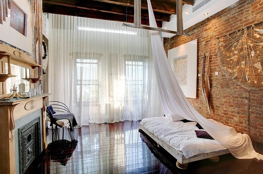 Loft-style bedroom with high ceiling, wooden beams and low-slung...