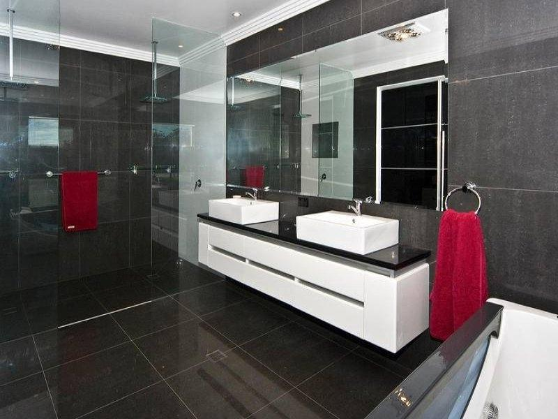Modern bathroom design with built-in shelving using frameless...