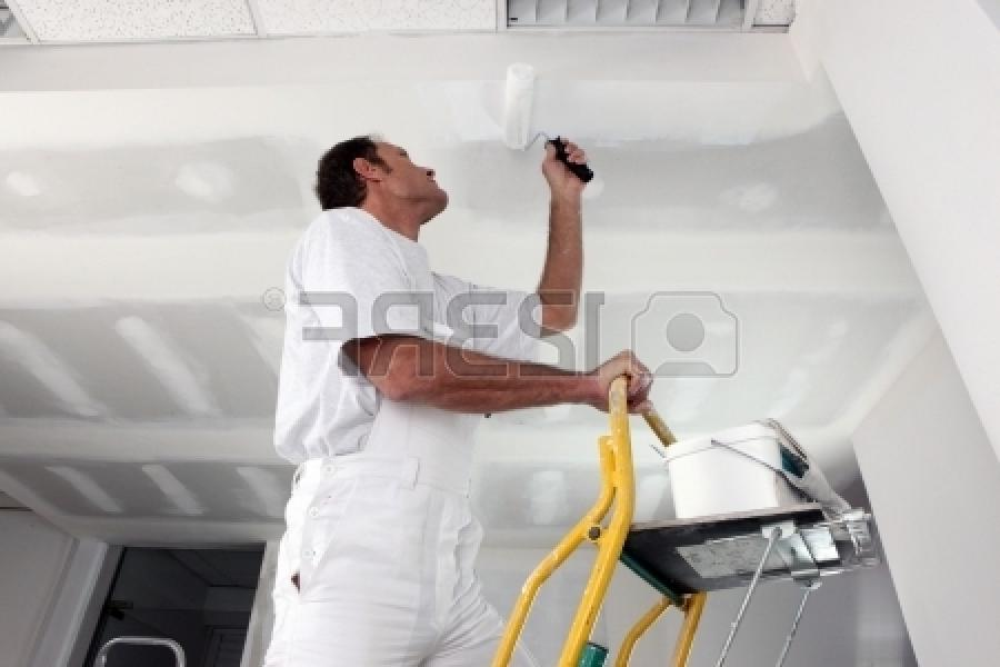 Stock Photo - Tradesman painting a ceiling