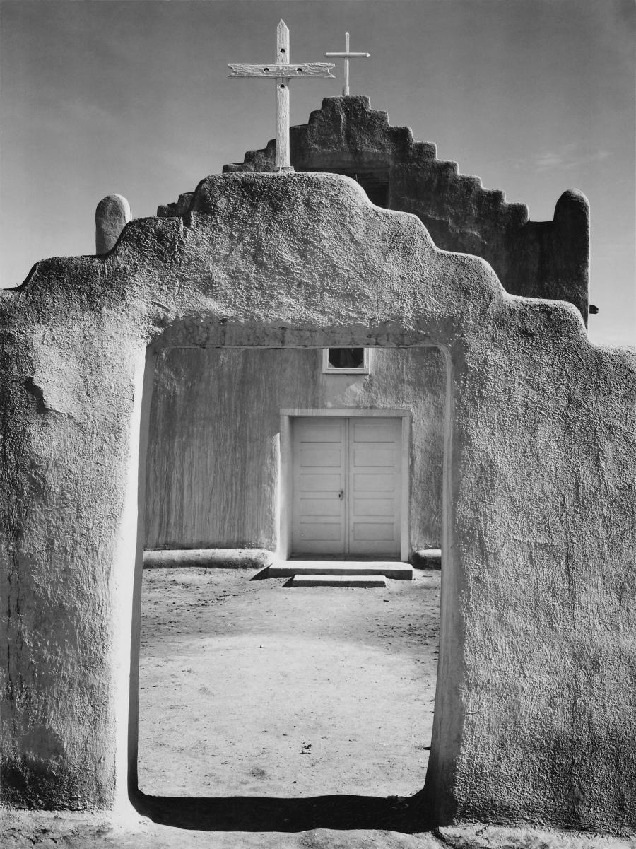 A black-and-white vertical photograph shows an adobe wall in the...