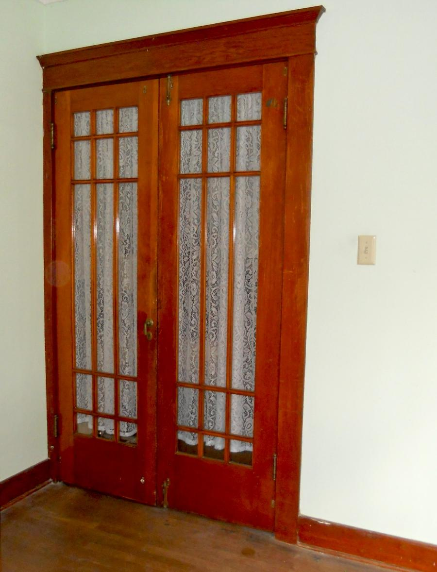 Gorgeous original interior French doors separating living room...