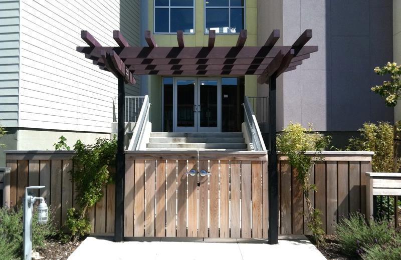 A redwood gate with a pergola marks an entryway.
