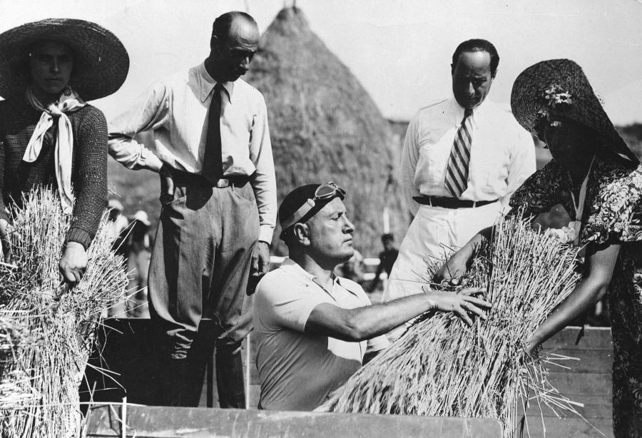 Benito Mussolini with farmers, taking part in the first threshing...