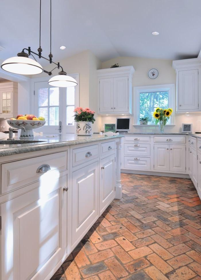 Basic white kitchen with #brick flooring. Holds the heat in the...