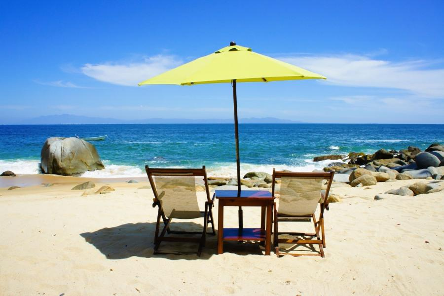 Set on the sand facing the ocean two chairs flank a small table