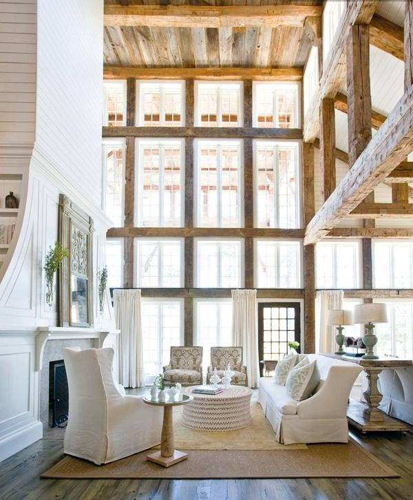 ... white kitchen thatu grounded with the wood beams that cross...