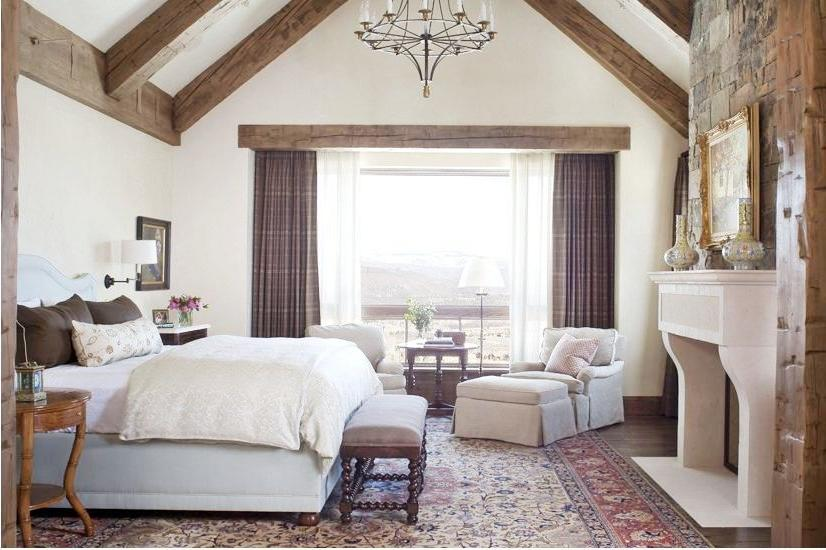 Rustic country bedroom with fireplace and exposed ceiling beams