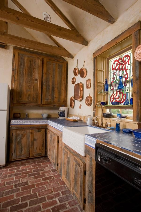 The kitchen features a brick floor and cabinets made from the...