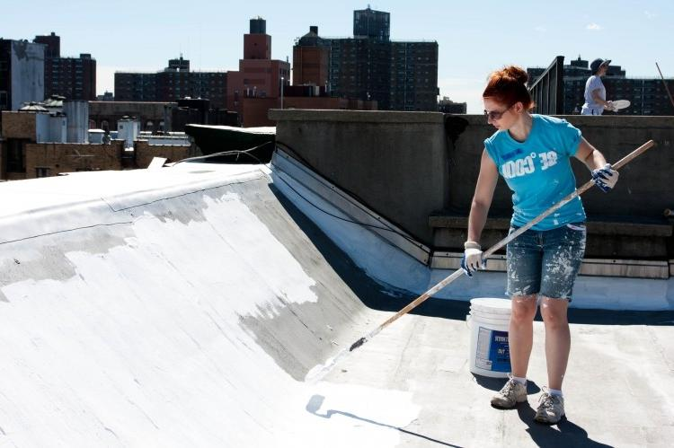 COOLING OFF: A volunteer paints the roof of 65 E. Fourth St....